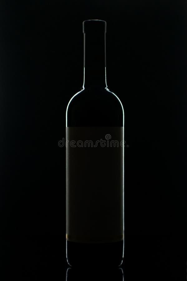 En flaska av rött vin med ett exponeringsglas och druvor royaltyfri fotografi