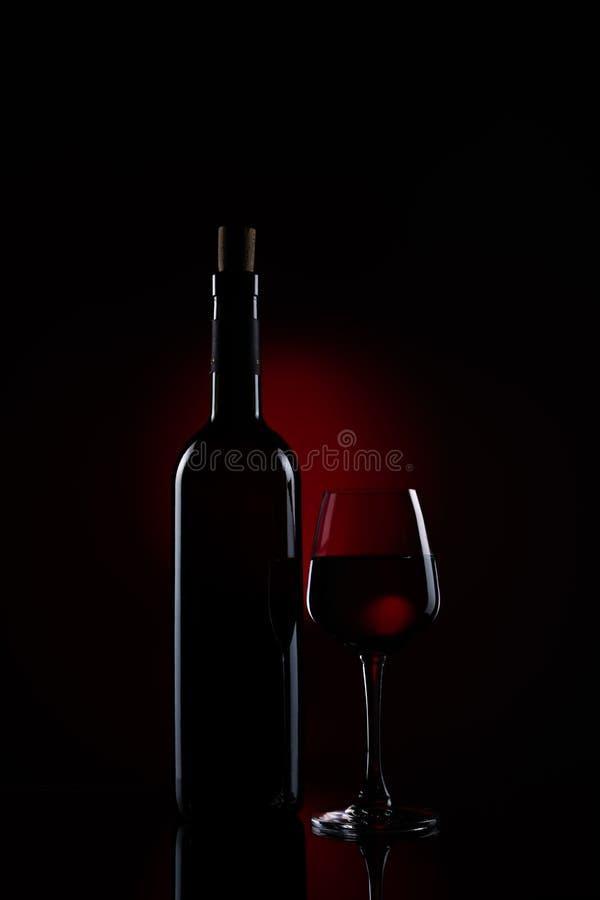 En flaska av rött vin med ett halvfullt vinexponeringsglas arkivfoto