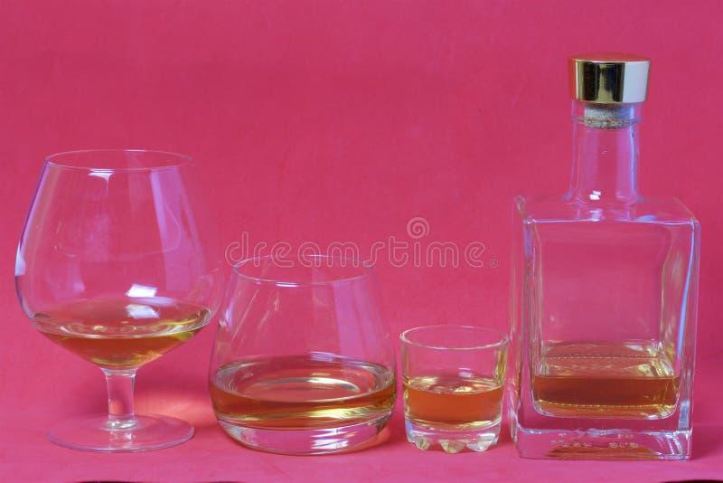 En flaska av stark alkohol Exponeringsglas och en bunt med en stark alkoholdryck som hälls in i dem arkivfoto