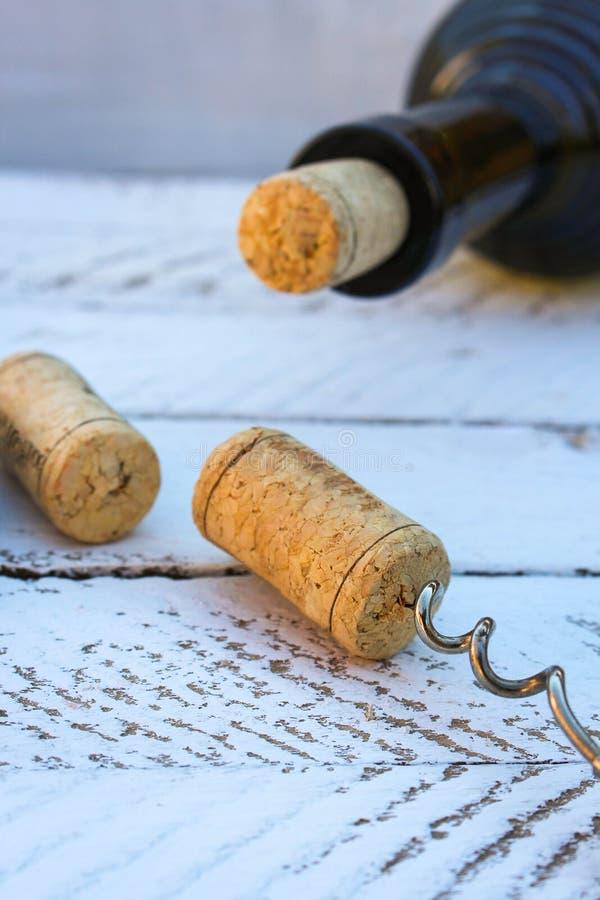 En flaska av vin och en korkskruv i korken på träbakgrund royaltyfri bild