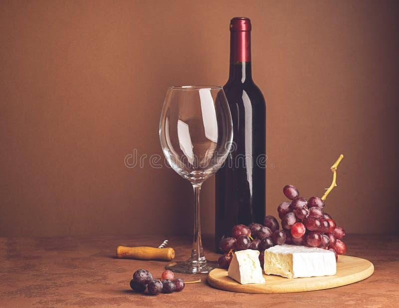 En flaska av vin per den tomma exponeringsglasgruppen av r?da druvor en skiva av ost p? en m?rk bakgrund kopiera avst?nd Selektiv arkivbild