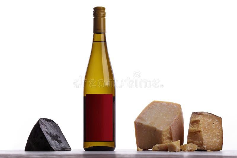 En flaska av vitt vin, dyr ost, unken ost, svart ost royaltyfri foto