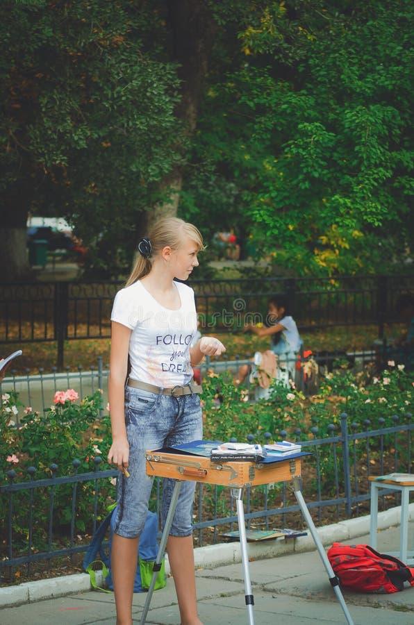 En flicka är attraktioner för en elev för konstskola i parkera royaltyfri fotografi