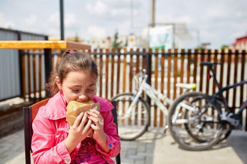En flicka äter en osthamburgare i kafét för öppen luft framme av cykelparkeringsplatsen arkivfoton