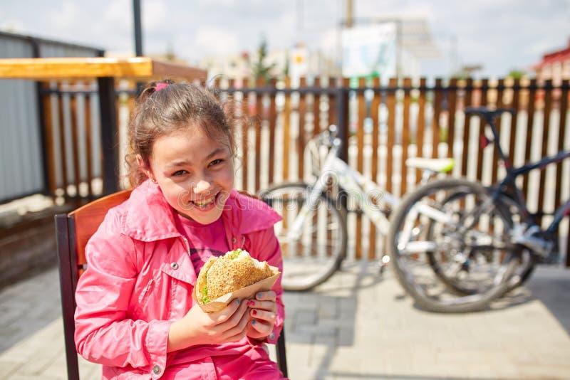 En flicka äter en osthamburgare i kafét för öppen luft framme av cykelparkeringsplatsen royaltyfria foton