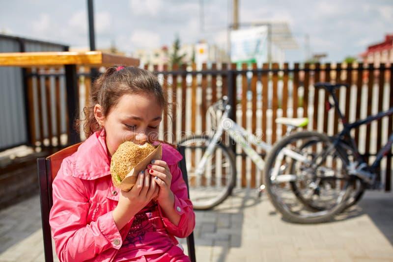 En flicka äter en osthamburgare i kafét för öppen luft framme av cykelparkeringsplatsen royaltyfri fotografi