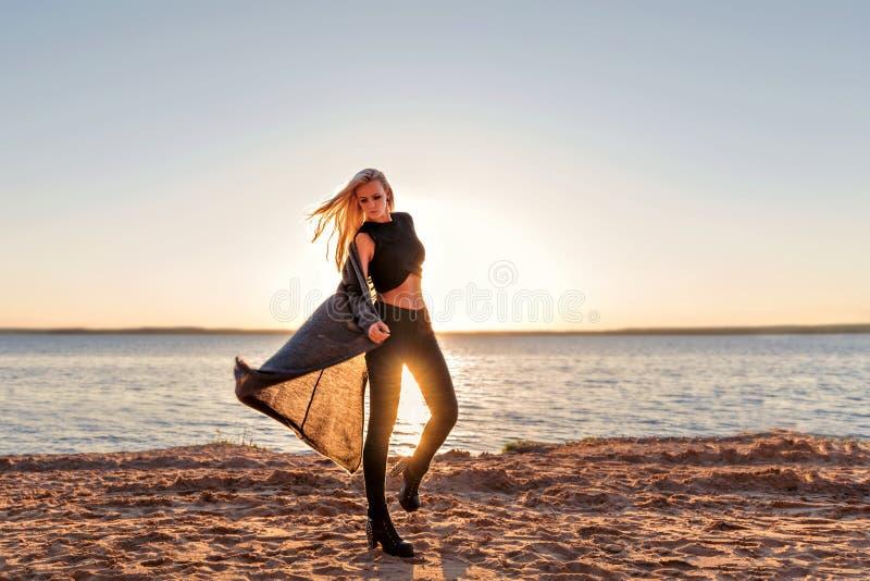 En flicka av sportiga moment för en kropp in i dansen och promenerar den sandiga stranden på gryningen av solen i mörk kläder som arkivbilder