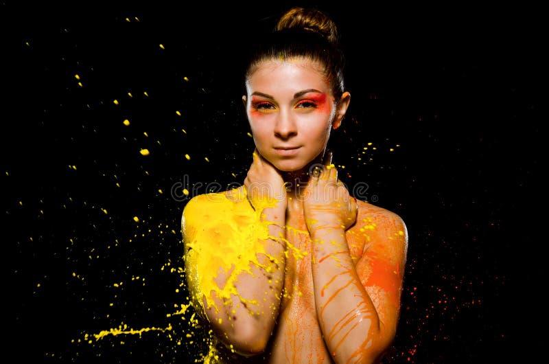 En flicka badas i gul målarfärg på en sida och orange målarfärg på annan Flickan täcker henne bröst med hennes händer och c arkivbilder