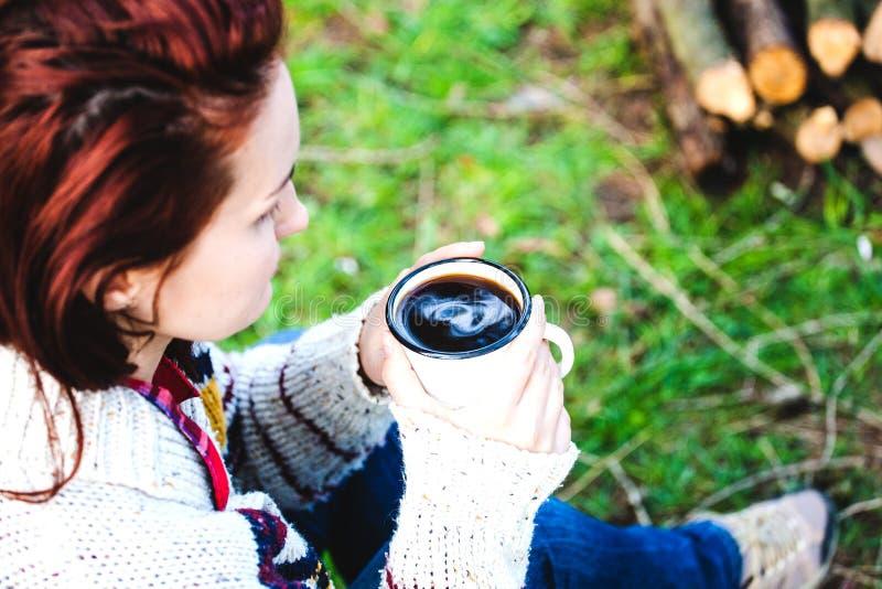 En flicka dricker kaffe vid branden royaltyfri foto
