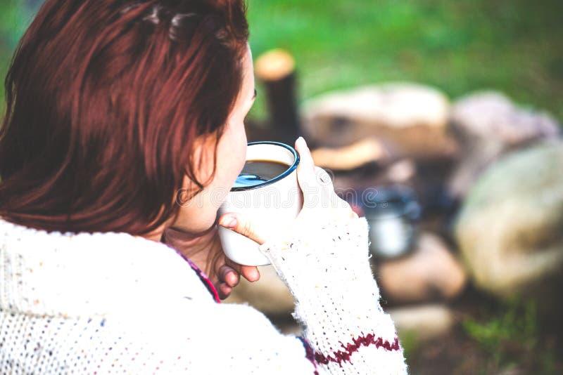 En flicka dricker kaffe vid branden royaltyfria bilder