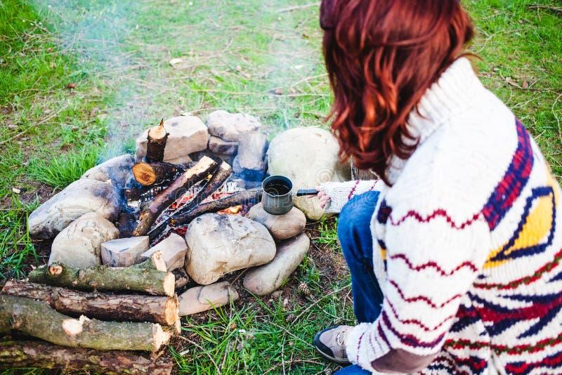 En flicka dricker kaffe vid branden arkivfoton