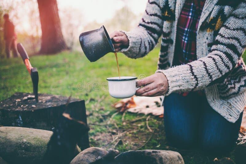 En flicka dricker kaffe vid branden fotografering för bildbyråer