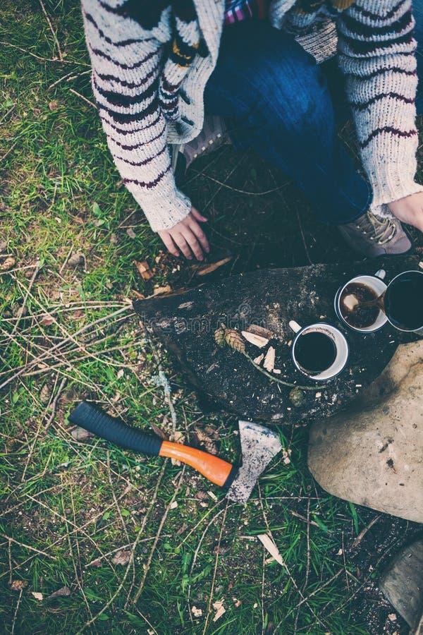 En flicka dricker kaffe vid branden arkivbild