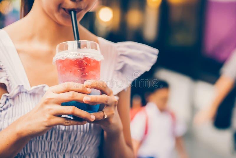 En flicka dricker vatten från ett exponeringsglas till och med ett sugrör royaltyfri foto