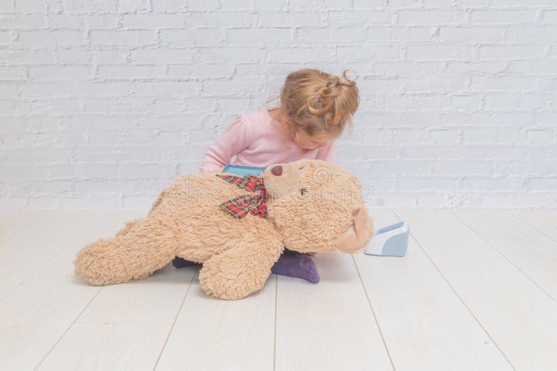 En flicka, ett barn som spelar doktorn, mått trycket av en björn royaltyfri fotografi
