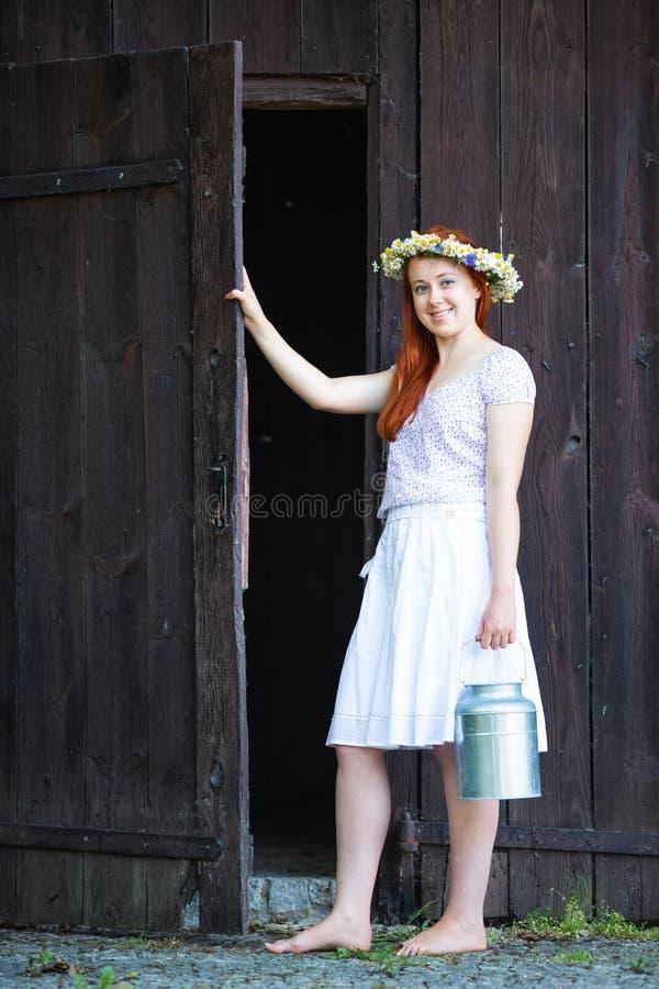 En flicka från byn med en hink av mjölkar arkivfoto