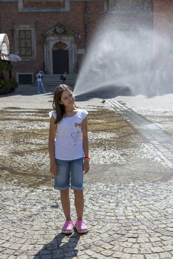 En flicka framme av en springbrunn i marknadsfyrkanten av Wroclaw, Polen royaltyfri fotografi