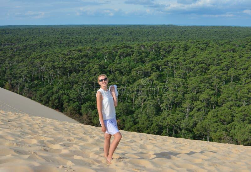 En flicka i bakgrunden av en barrskog på den Pyla dyn, den största sanddyn i Europa royaltyfria foton