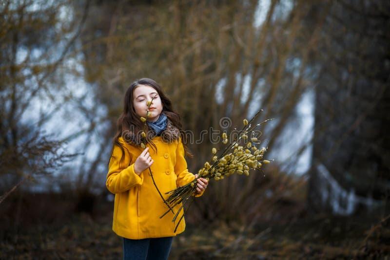 En flicka i ett gult lag i skogen i tidig vår med en pilfilial av ris En flicka som pälsfodrar fresheten eller högt vatten arkivfoto