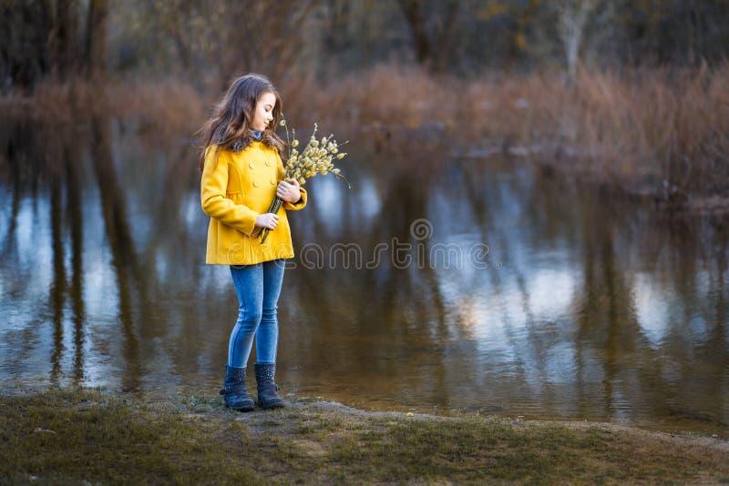 En flicka i ett gult lag i skogen i tidig vår med en pilfilial av ris En flicka som pälsfodrar fresheten eller högt vatten arkivbilder