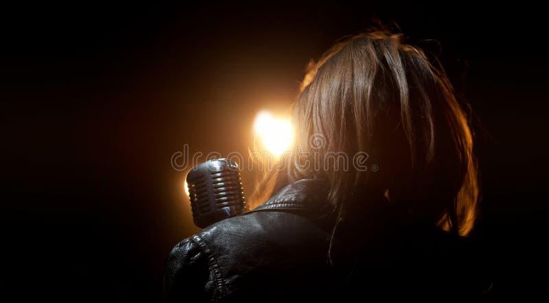 En flicka i ett läderomslag med en mikrofon i ljuset arkivfoto