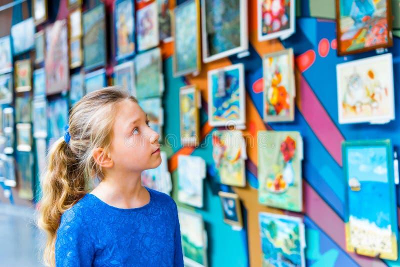 En flicka i ett museum på en utställning av målningstudier konst, undersökande målningar av berömda författare av målare royaltyfri fotografi