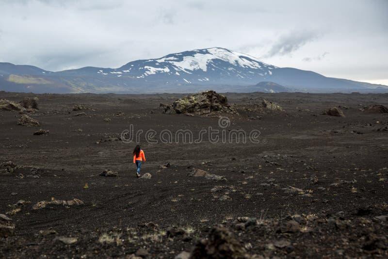 En flicka i ett orange omslag går till och med ett utbränt lavafält royaltyfria foton