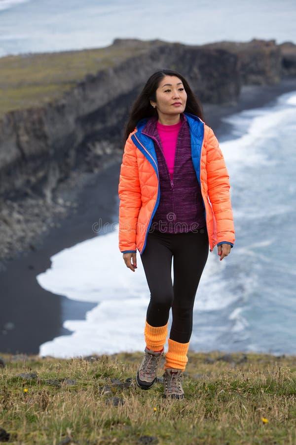 En flicka i ett orange omslag promenerar en stenig havkust som sträcker till horisonten royaltyfria bilder