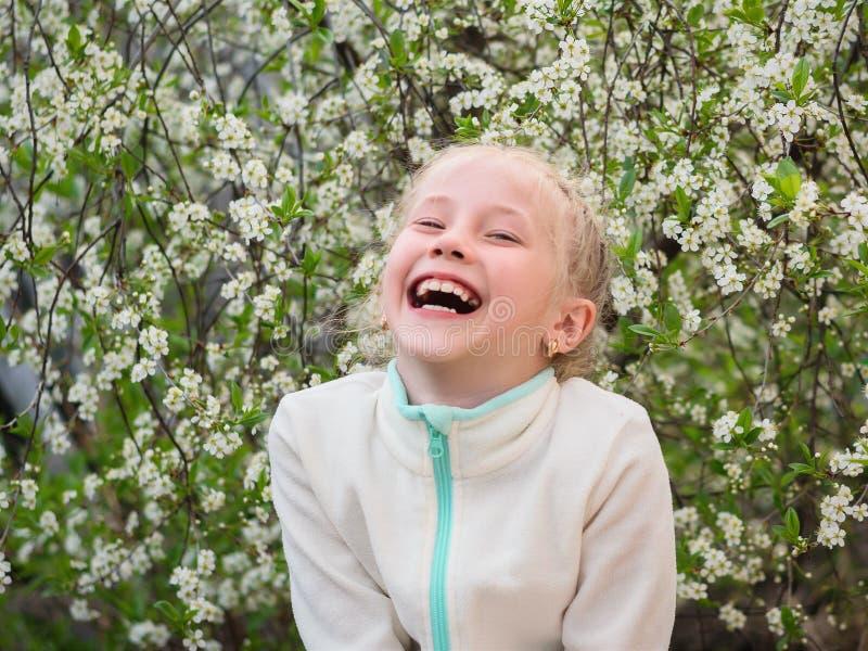 En flicka i ett sportomslag skrattar i en vårkörsbär parkerar glatt royaltyfri foto