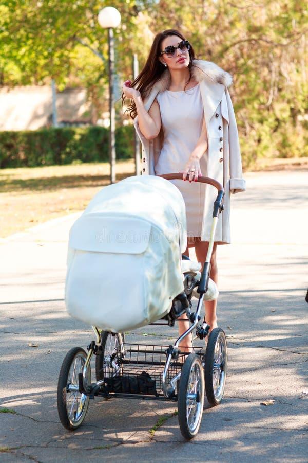 En flicka i exponeringsglas går med en sittvagn arkivbild
