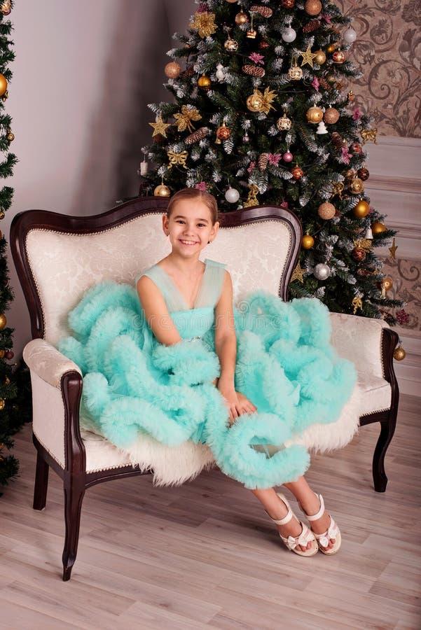 En flicka i en frodig blå klänning sitter på soffan nära julgranen royaltyfri fotografi
