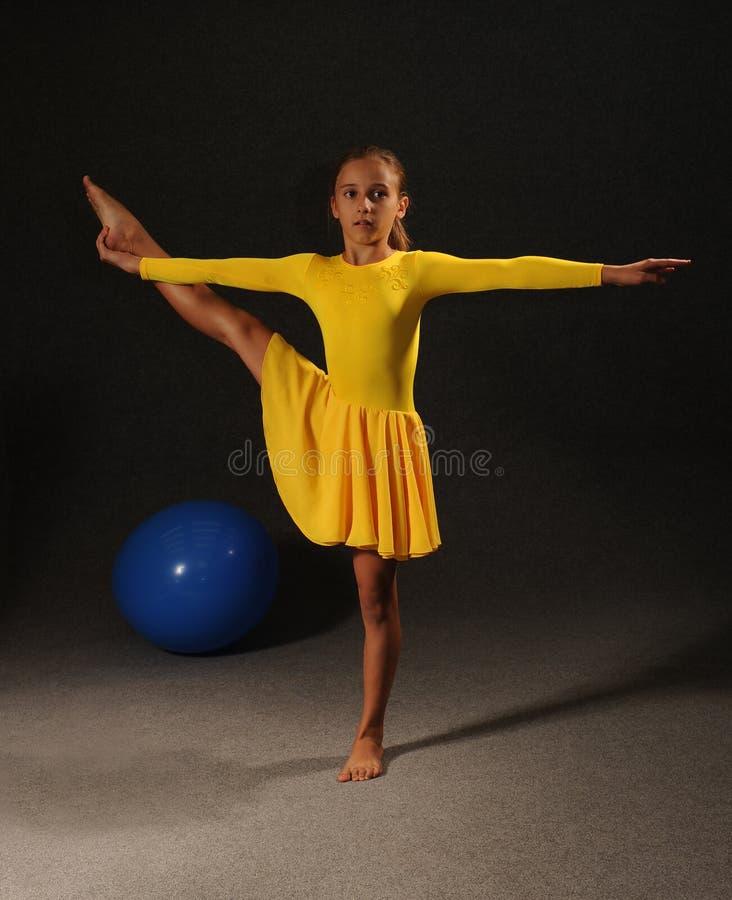 En flicka i en gul klänning i idrottshallen är förlovad i gymnastik royaltyfri bild