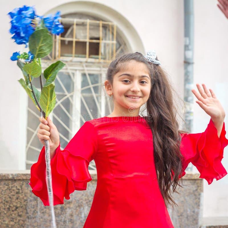 En flicka i en härlig klänning på en festlig procession av kandidater av skolor arkivfoton
