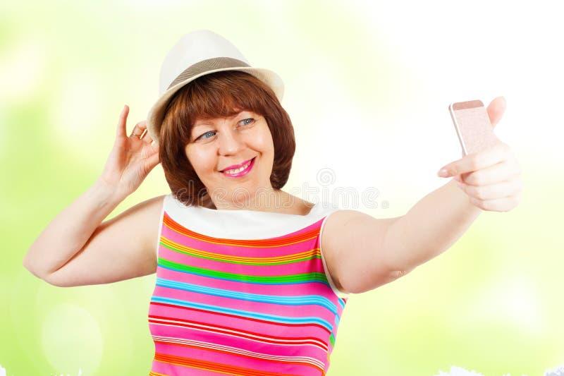 En flicka i en hatt gör selfie arkivbild