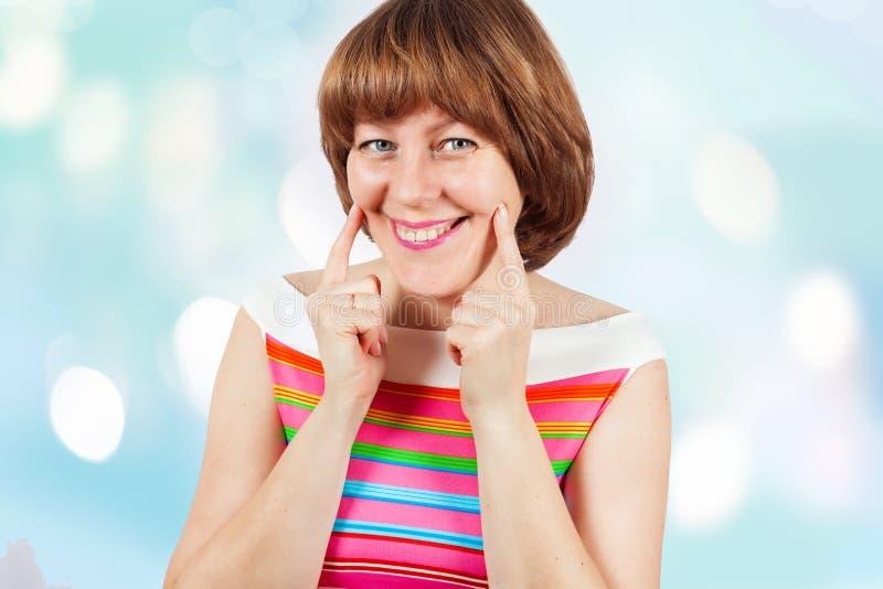 En flicka i en ljus T-tröja ler och ser kameran fotografering för bildbyråer