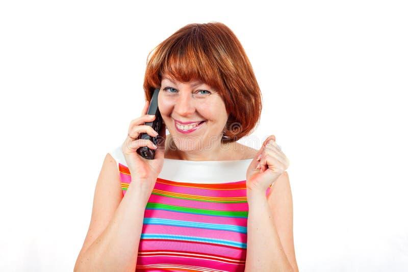 En flicka i en ljus T-tröja talar på telefonen och le arkivbild