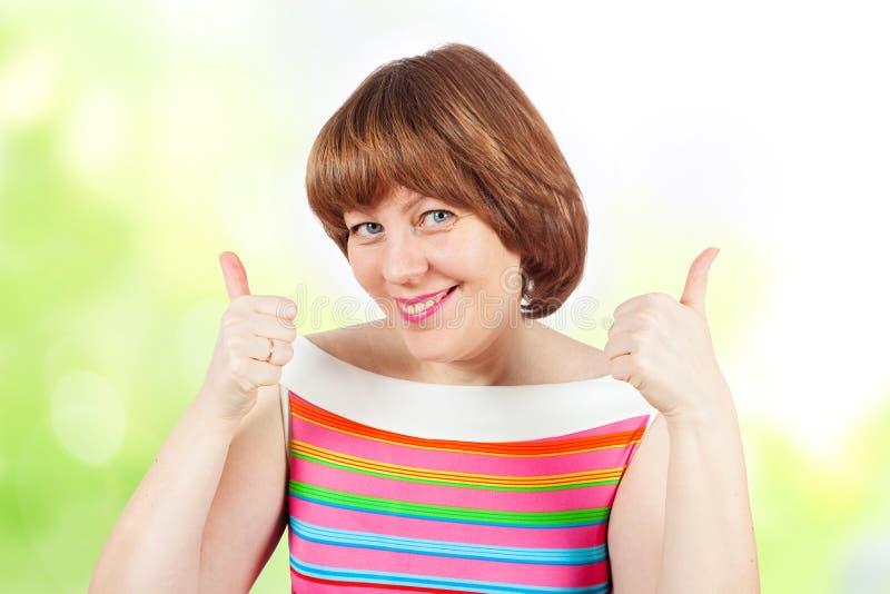 En flicka i en ljus T-tröja visar upp tummar royaltyfria bilder