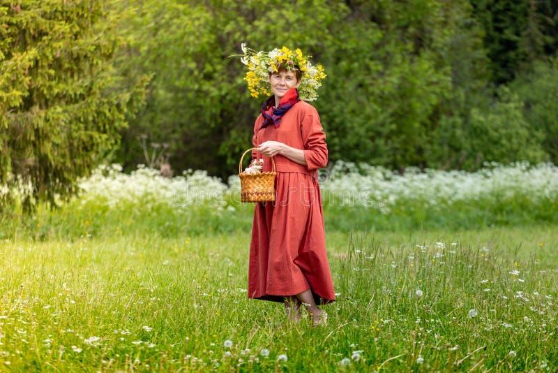 En flicka i en nationell dräkt och en krans på hennes huvud samlar bär i en korg, på en grön gräsmatta in fotografering för bildbyråer