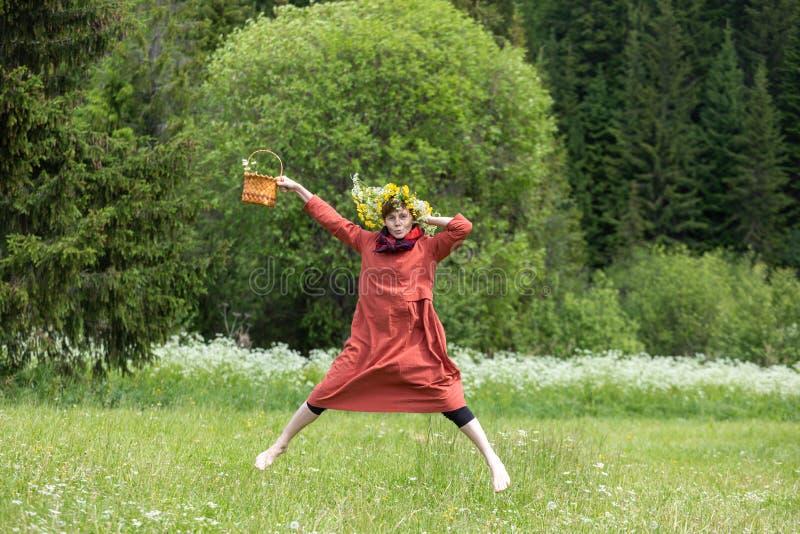 En flicka i en nationell dräkt och en krans på hennes huvud samlar bär i en korg, på en grön gräsmatta in royaltyfri foto