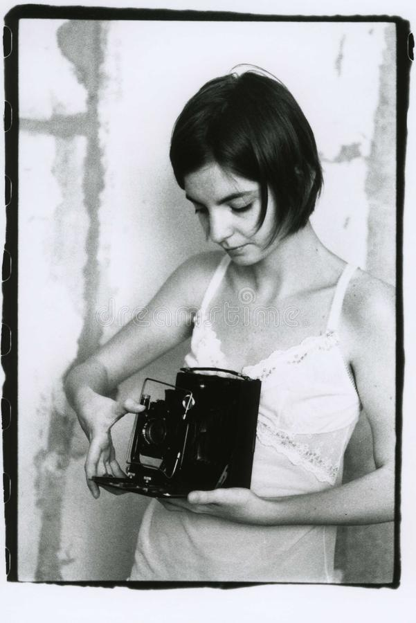 En flicka i en nattlinne rymmer en tappningkamera för stort format arkivbilder