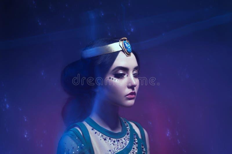 En flicka i orientalisk dress, drottning av stormen Prinsessa Jasmine Bakgrunden är en vridning och en stark vind studio fotografering för bildbyråer
