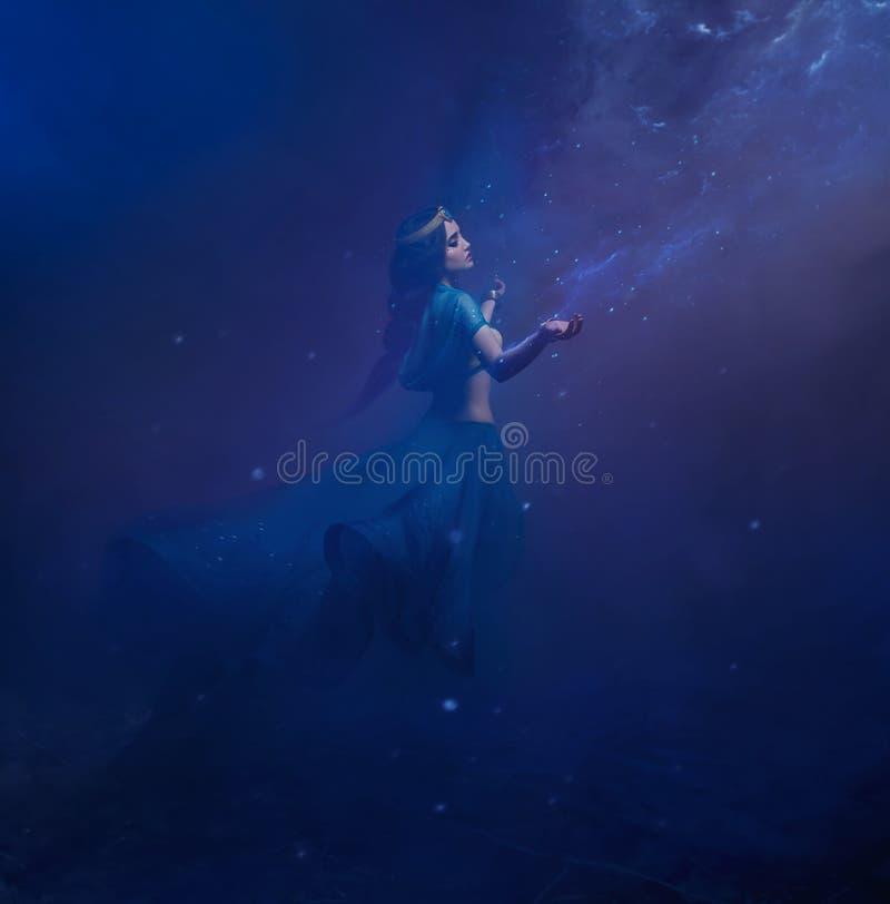 En flicka i orientalisk dress, drottning av stormen Prinsessa Jasmine Bakgrunden är en vridning och en stark vind studio arkivbild