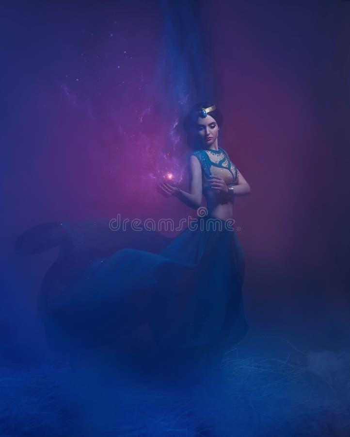 En flicka i orientalisk dress, drottning av stormen Prinsessa Jasmine Bakgrunden är en vridning och en stark vind studio arkivfoton