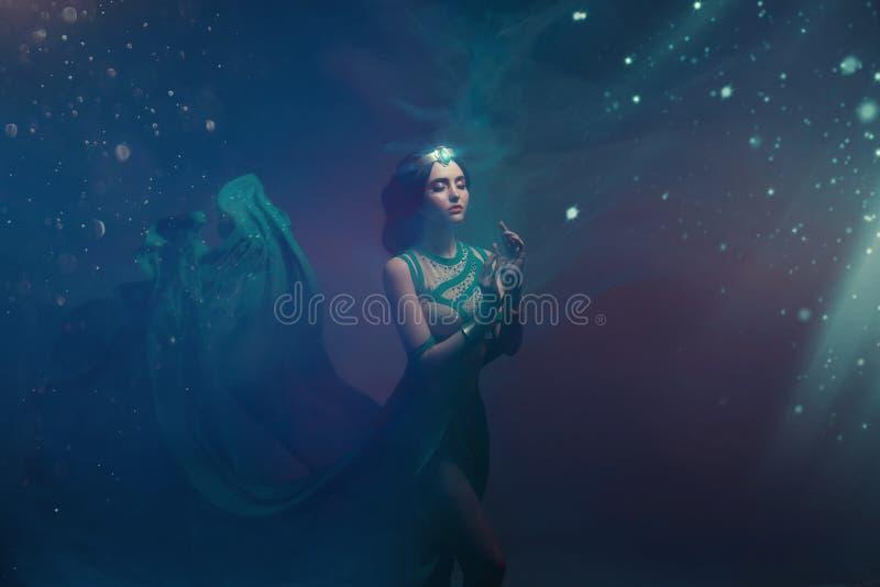 En flicka i orientalisk dress, drottning av stormen Prinsessa Jasmine Bakgrunden är en vridning och en stark vind studio royaltyfria foton