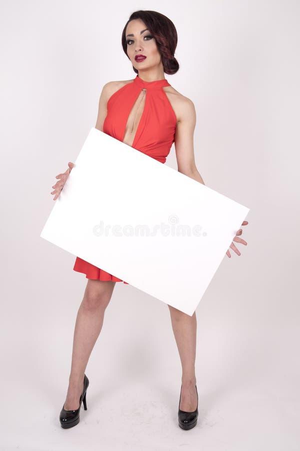 En flicka i en röd klänning med höga häl och en skylt royaltyfria bilder