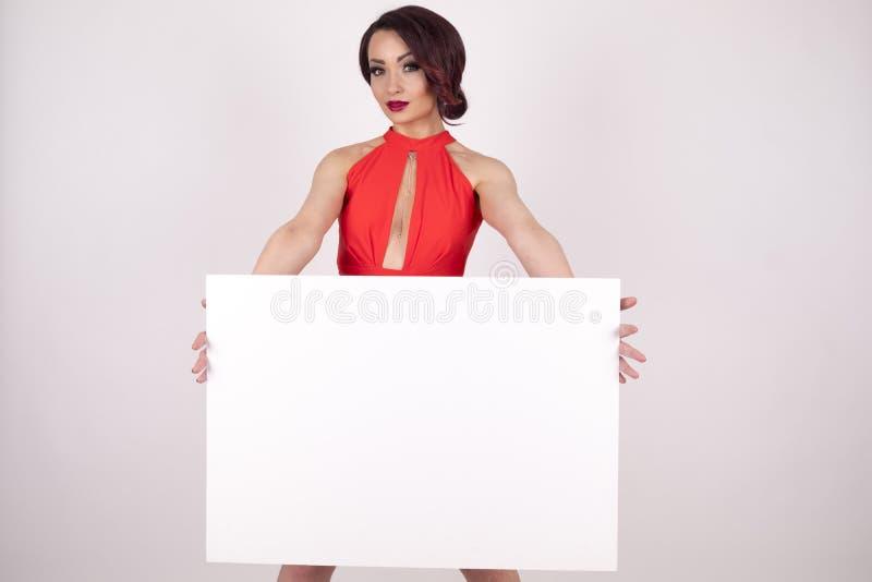 En flicka i en röd klänning med en skylt royaltyfri bild