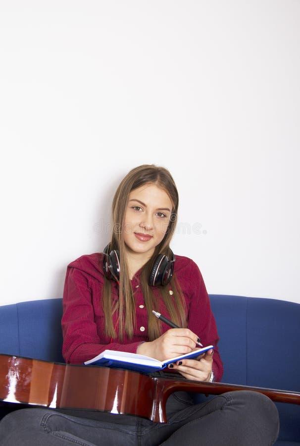 En flicka i en röd skjorta Skriv en sång i en blå anteckningsbok royaltyfri fotografi