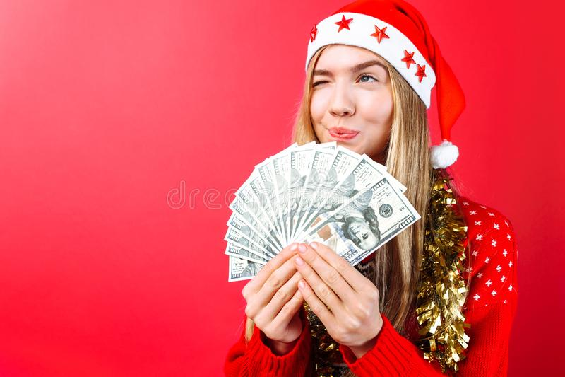 En flicka i en röd tröja och en jultomtenhatt, rymmer pengarna och blickarna som tänker bort var att spendera den på en röd bakgr royaltyfri bild