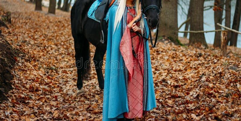 En flicka i en rosa tappningklänning, med långt hår, en blondin i en blått, gammalmodig udde, ställningar bredvid en häst, tog he royaltyfri bild