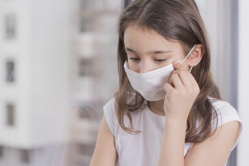 En flicka i en skyddsmask från virus sitter vid fönstret, masken för att skydda Covid-19 Flickan blev sjuk och kan inte gå ut royaltyfri fotografi